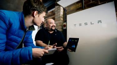 Conversation in front of a Tesla Powerwall II