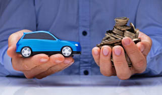 Hands holding a toy car and coins