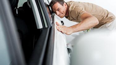 man stroking car