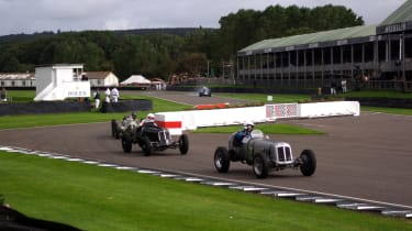 A trio of 1930s and 1940s Grand Prix cars races through the chicane on the Goodwood Motor Circuit.