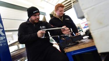 Student mechanics working on classic car