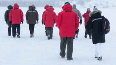 Group walking frozen lake