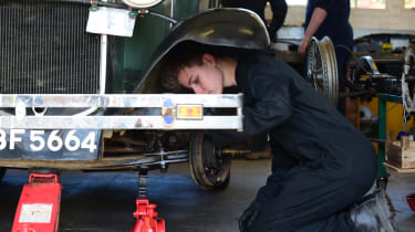 Student mechanic inspecting classic car