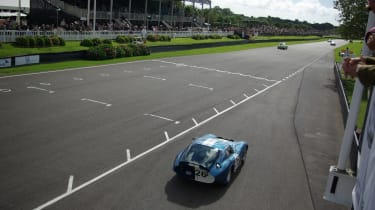 One of the six Shelby Daytona Coupes that were at this year's event exits the pit lane.
