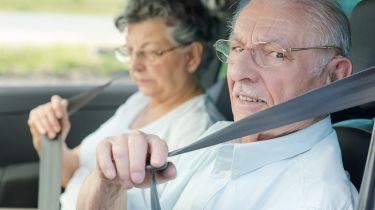 old couple putting on seatbelts